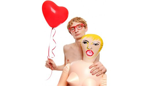A young man holding sex doll for men with a balloon in hand